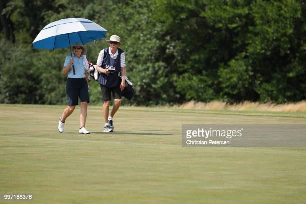 Barb Moxness walks the eighth fairway with her caddie during the first round of the US Senior Women's Open at Chicago Golf Club on July 12 2018 in...