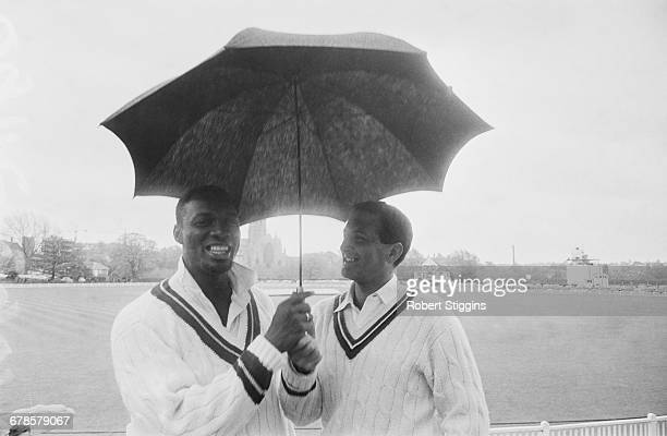 Barbadian cricketer Wes Hall and England cricketer Basil D'Oliveira share an umbrella during a holdup in play between the West Indies and Worcester...
