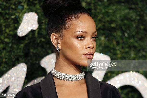 Barbadian pop star Rihanna poses for pictures on the red carpet upon arrival to attend the British Fashion Awards 2014 in London on December 1 2014...