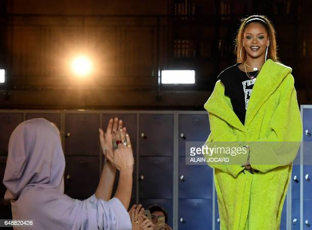 Barbadian singer Rihanna is applauded by English fashion model Cara Delevingne during Rihanna's Fenty Collection from PUMA women's FallWinter...
