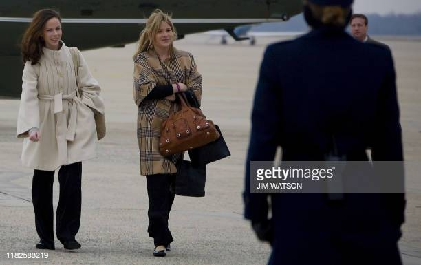 Barbara and Jenna Bush the daughters of US President George W Bush are greeted by Air Force Security as they prepare to board Air Force One at...