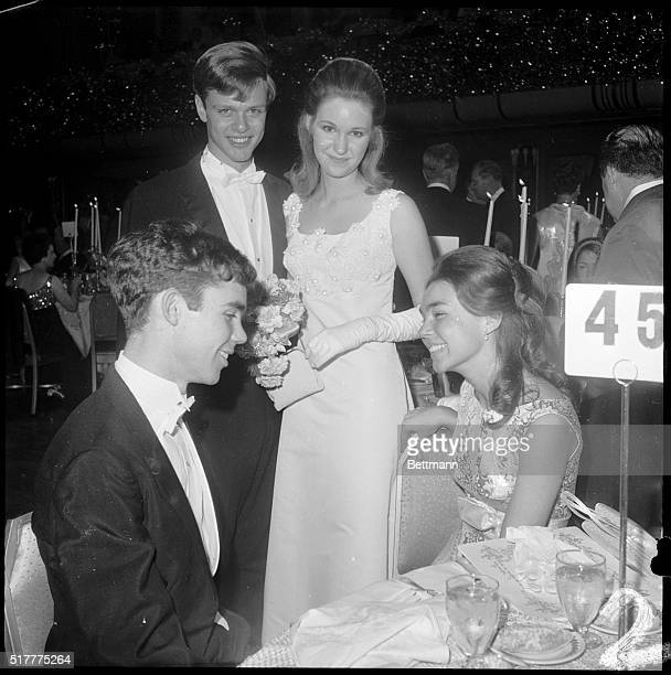 Barbara Anne Eisenhower and her escort Don Stolper table hop at the International Debutante Ball at the Waldorf December 28th to visit her brother...