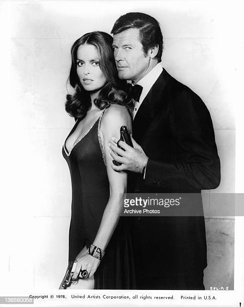 Barbara Bach and Roger Moore posing with pistols in each of their left hands in a scene from the film 'The Spy Who Loved Me' 1977