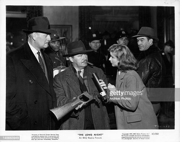 Barbara Bel Geddes leaning on man holding weapon in a scene from the film 'The Long Night', 1947.