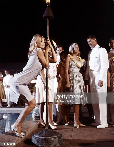 Barbara Bouchet holds onto a torch in a scene from the film 'In Harm's Way' 1965