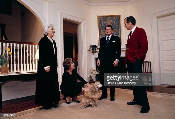 Barbara Bush, First Lady Nancy Reagan, President Ronald Reagan, Vice President George H.W. Bush stand around the Bush's Golden Cocker Spaniel at the...