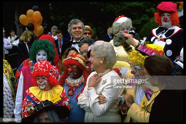 Barbara Bush Mrs VP Marilyn Quayle amid colorful crew of clowns celebrating Halloween on WH grounds