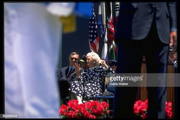 Barbara Bush schmoozing w secret servicemantype exhibiting rare smile in stands during Air Force Academy Falcon Stadium graduation fete
