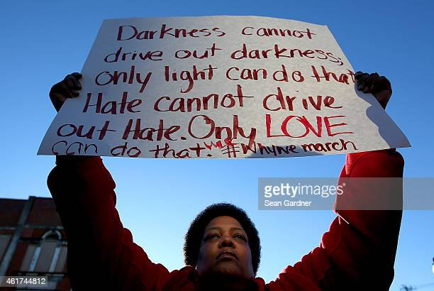 Barbara Carter holds up a sign as thousands marched across the Edmund Pettus Bridge along with members of the cast of the movie Selma in honor of Rev...