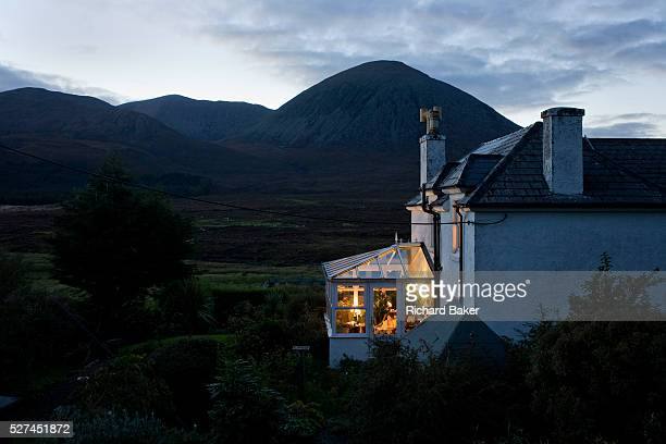 Barbara Christie sits alone in her conservatory at Swordale House overlooking Beinn Na Caillich mountain. It is nearly dark at this northern latitude...