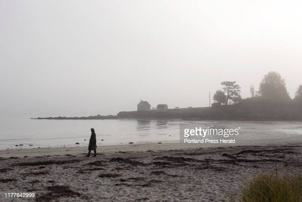 Barbara Corey of South Portland takes her daily walk along Willard Beach as the fog begins to burn off on Monday Oct 21 2019