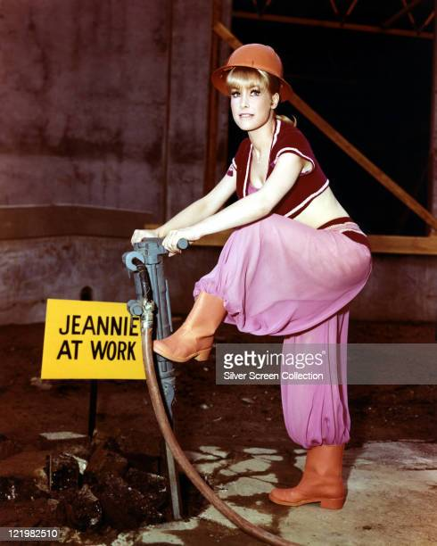 Barbara Eden US actress in costume posing with a pneumatic drill and wearing a hard hat alongside a sign reading 'Jeannie at work' in a publicity...