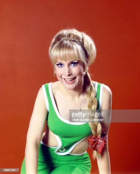 Barbara Eden US actress wearing a green and white outfit smiling with her hair plaited with a red bow in a studio portrait against a red background...
