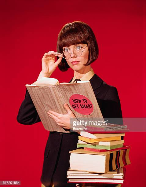 Barbara Feldon as 'Control Agent 99' tipping her reading glasses as she holds a book entitled How To Get Smart This is a publicity photo for the TV...