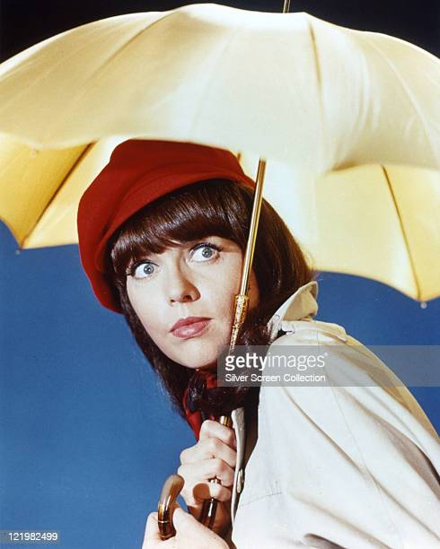 Barbara Feldon US actress poses wearing a red beret and holding a yellow umbrella open above her head in a publicity portrait for the US television...