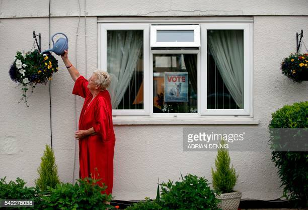 Barbara House who supports Brexit waters her plants outside her house while a poster advertising Britain leaving the EU is attached to her window in...