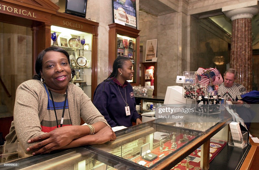 Barbara Kidwell, who has worked for the U.S. Capitol Gift Shop for about five years, relaxes on the counter while her co-worker, Zabrina Smith, a two year employee, answers questions for tourists.