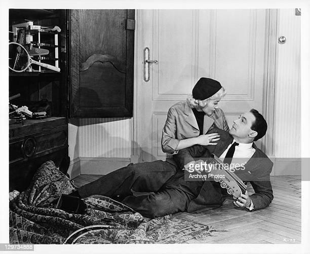 Barbara Laage and Gene Kelly down on the floor together in a scene from the film 'Happy Road' 1957