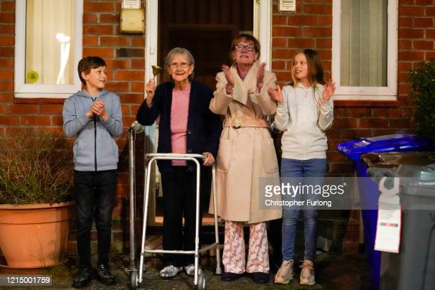 Barbara Leigh, aged 93, rings a bell for the NHS, with her family who are all staying together throughout the lockdown, from their front garden...
