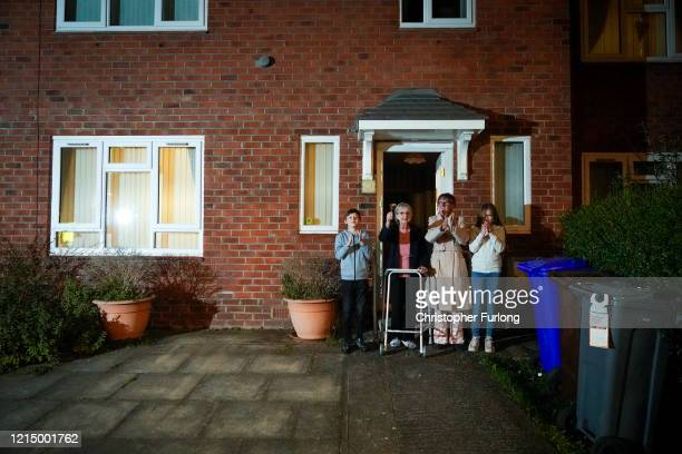 Barbara Leigh aged 93 rings a bell for the NHS with her family who are all staying together throughout the lockdown from their front garden across...