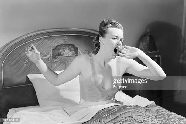 Barbara Lewis, in nightgown, sits up and yawns while in bed. Undated photograph.
