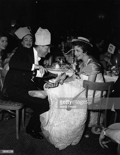 Barbara Lyons and Bebe Daniels watching Ben Lyon filling Edana Romney's slipper with champagne at the Limelight Ball at the Savoy Hotel