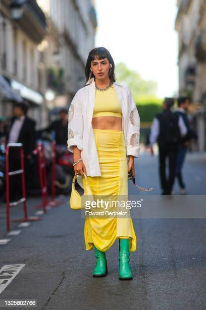 Barbara Malewicz wears sunglasses, a metallic chain silver necklace, a pale yellow cropped tank top, a white oversized shirt with mesh parts on the...