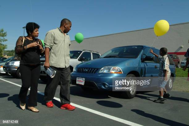 Barbara Megret left and Jorge Luis Ferrer watch Jorge Ferrer reach for a balloon tied to a Ford Windstar van at Fucillo Hyundai in Syracuse New York...