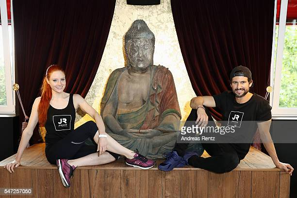 Barbara Meier and Tom Beck sit next to a giant Buddha sculpture at John Reed Fitness on July 14 2016 in Bonn Germany John Reed Fitness launches today...
