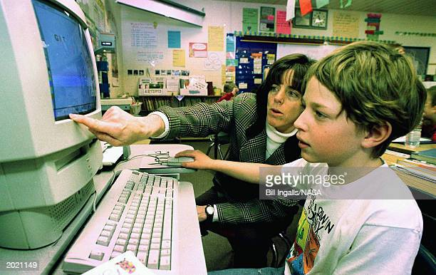 Barbara Morgan looks at a computer with one of her students at McCall Elementary School June 31 1998 in McCall Idaho Morgan is slated to become the...