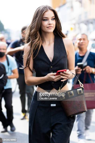 Barbara Palvin, wearing a grey pinstripe vest with matching pants and Etro bag, poses ahead of the Etro fashion show during the Milan Fashion Week -...