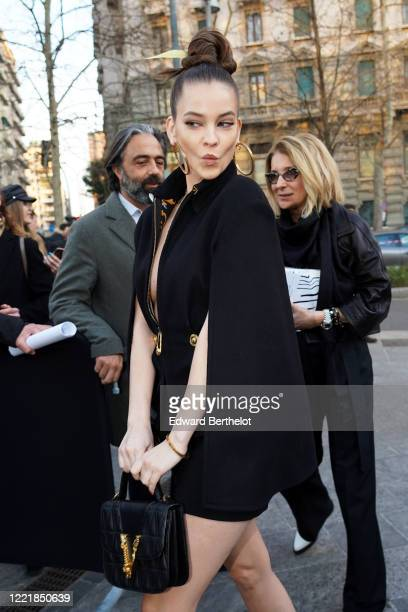 Barbara Palvin wears earrings, a black low neck dress / Jacket, outside Versace, during Milan Fashion Week Fall/Winter 2020-2021 on February 21, 2020...