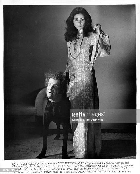 Barbara Parkins with her black Labrador wearing human head as a mask in a scene from the film 'The Mephisto Waltz' 1971