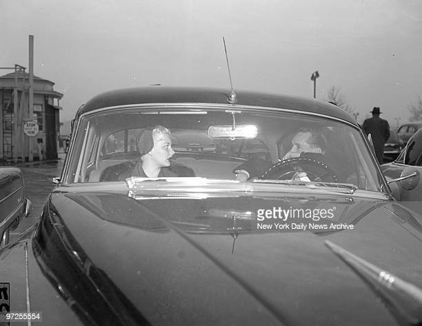Barbara Payton in flaming red ensemble with lips to match and Franchot Tones depart LaGuardia Airport after Payton's arrival from Coast