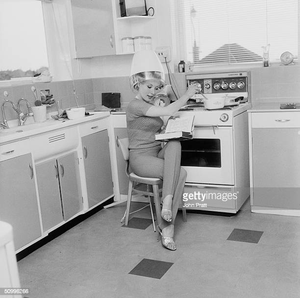 Barbara Roscoe does a spot of cooking while under a hairdryer at her home 23rd May 1963 She is appearing in an Elstree film 'Crooks in Cloisters'
