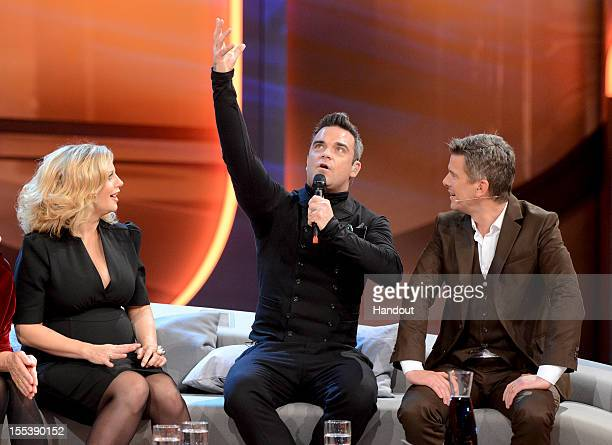 Barbara Schoeneberger and Robbie Williams meet while Markus Lanz looks on during the 'Wetten dass' show on November 3 2012 in Bremen Germany