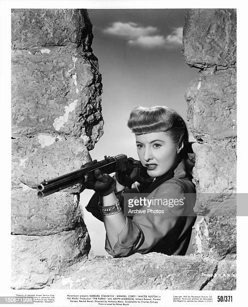 Barbara Stanwyck aiming rifle in publicity portrait for the film 'The Furies' 1950