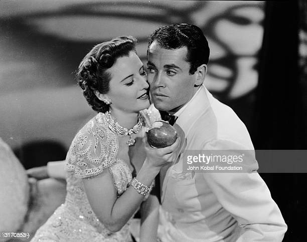 Barbara Stanwyck encourages Henry Fonda to take a bite of the apple in the romantic comedy 'The Lady Eve' directed by Preston Sturges