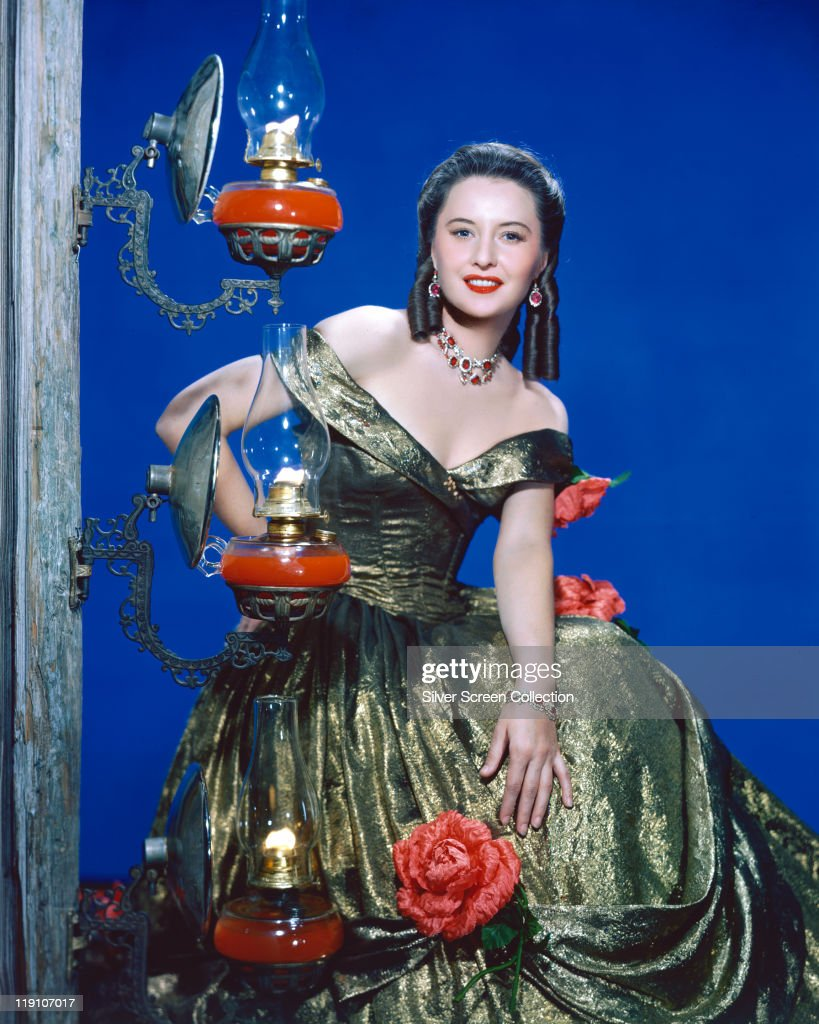 Barbara Stanwyck (1907-1990), US actress, poses by an ornate lamp, wearing a green gown, in a studio portrait, against a blue background, in a publicity still for the film 'California', 1947.