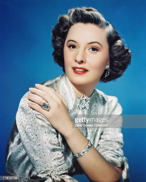 Barbara Stanwyck US actress poses in a studio portrait against a blue background circa 1950
