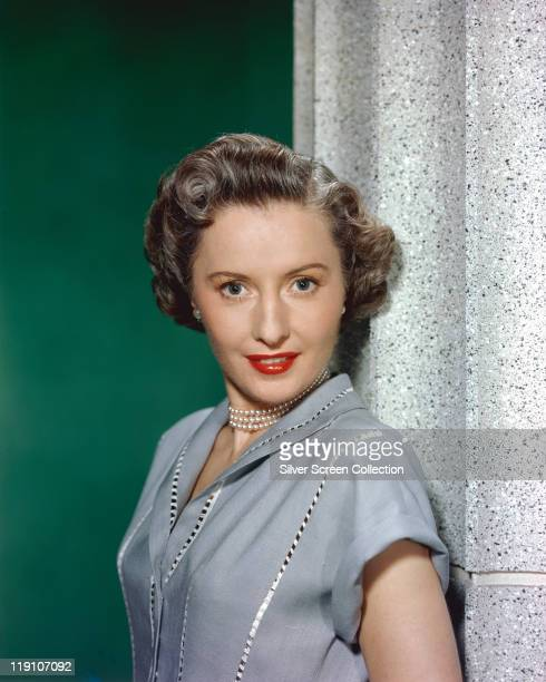 Barbara Stanwyck US actress poses in a studio portrait against a green background circa 1950