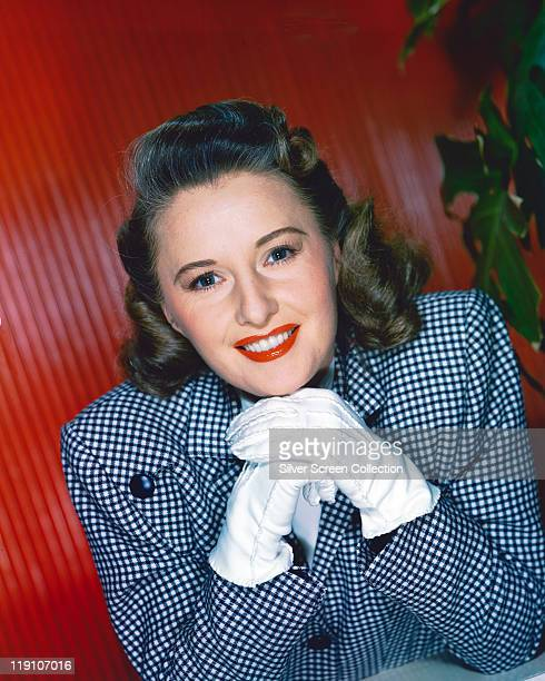Barbara Stanwyck US actress wearing a blueandwhite jacket and resting her chin on her hands in front of her wearing white gloves circa 1940