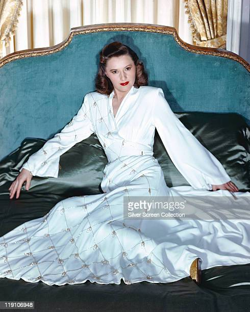 Barbara Stanwyck US actress wearing a long white dress reclining on a bed with silk bedding circa 1940