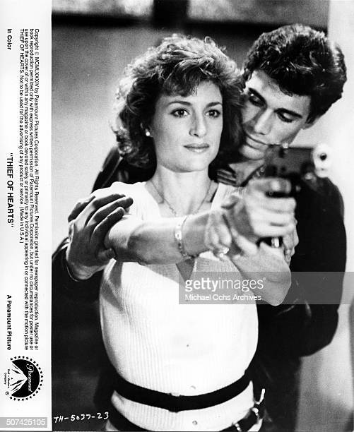 Barbara Williams learns how to shoot a gun from Steven Bauer in a scene from the Paramount Pictures movie Thief of Hearts circa 1984