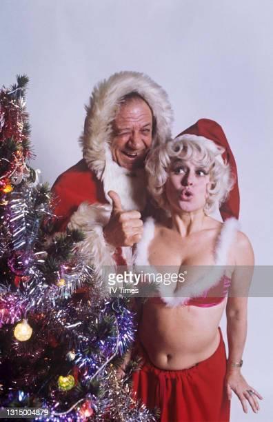 Barbara Windsor and Sid James dressed in santa outfits, circa 1973.