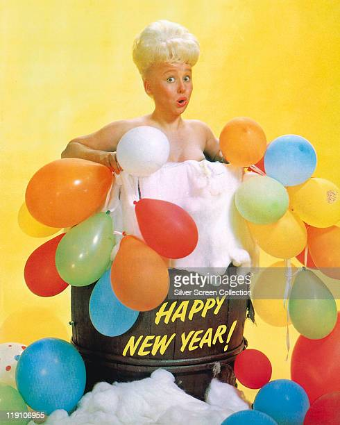 Barbara Windsor British actress poses in a barrel full of foam with balloons the barrel has 'Happy New Year' written on the side in a studio portrait...