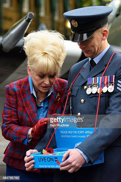 Barbara Windsor takes a poppy from servicemen at the launch of the British Royal Legion's London Poppy Day on October 29 2015 in London England...