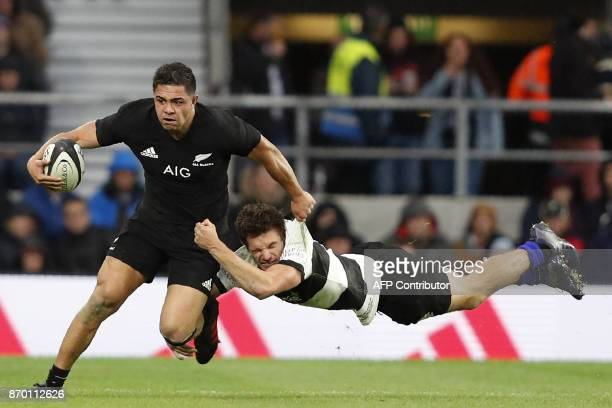Barbarians' New Zealand fullback George Bridge tackles New Zealand's centre Anton LienertBrown during the international rugby union match between...