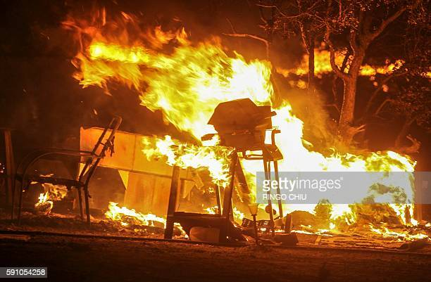 A barbecue and other items burn as the the Blue Cut wildfire rages near Cajon Pass north of San Bernardino California on August 16 2016 A rapidly...