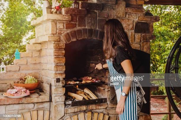 chef feminino de churrasco preparar alimentos no quintal de casa o fim de semana - tijolo material de construção - fotografias e filmes do acervo